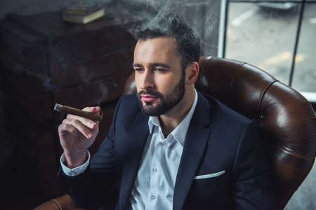 Handsome pensive man in suit is smoking cigar and looking away while sitting in leather chair indoors