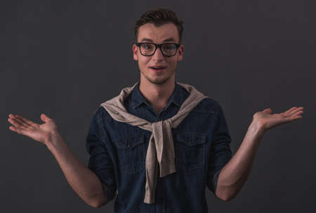 Handsome young man in glasses is lifting hands in dismay and looking at camera, on gray background Reklamní fotografie