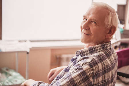 Handsome old man is looking at camera and smiling while sitting in wheelchair in hospital ward