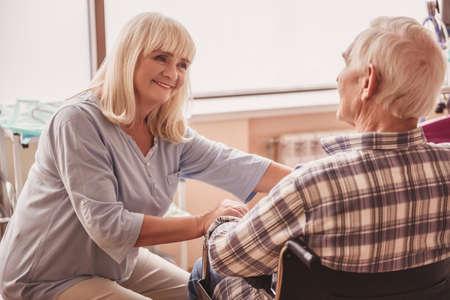 美しい老婦人は、彼が病院の病棟で車椅子に座っている間、彼女の夫と話し、笑顔です 写真素材 - 102322514