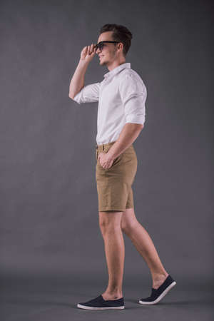 Full-length, back view image of handsome young man in shirt, shorts and sun glasses smiling while walking on gray background Zdjęcie Seryjne - 102395418