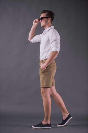 Volle Länge, Rückansichtbild des hübschen jungen Mannes im Hemd, in den Shorts und in der Sonnenbrille, die lächeln, während sie auf grauem Hintergrund gehen Standard-Bild