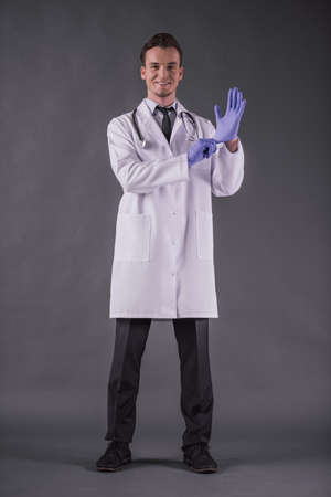 Full-length image of handsome young doctor in medical coat putting on gloves, looking at camera and smiling, on gray background