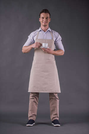 Full-length image of handsome young barista in apron holding a cup, looking at camera and smiling, on gray background