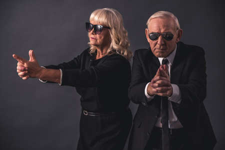 Beautiful old couple in elegant clothes and glasses is holding hands imitating guns, on gray background Foto de archivo
