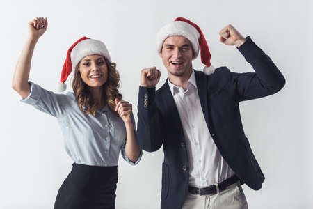 Handsome guy and beautiful girl in office clothes and Santa hats are raising fist, looking at camera and smiling, isolated on white