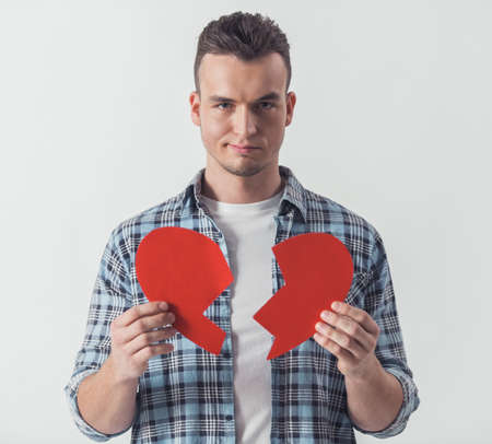 Handsome guy in casual clothes is holding two halves of big red paper heart, looking at camera and smiling, isolated on white Stock Photo