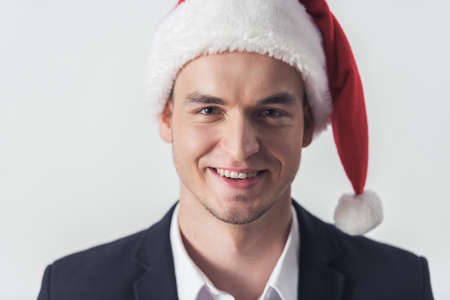 Handsome guy in suit and Santa hat is looking at camera and smiling, isolated on white