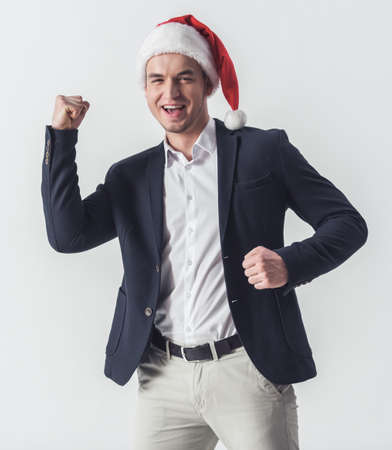 Handsome guy in suit and Santa hat is raising fist, looking at camera and smiling, isolated on white Stock Photo