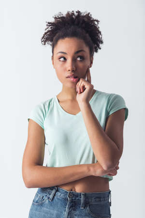Beautiful Afro-American girl in casual clothes is touching her cheek, biting her lip, looking away and thinking, isolated on white
