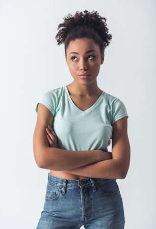 Pensive Afro-American girl in casual clothes is looking away and thinking, isolated on white