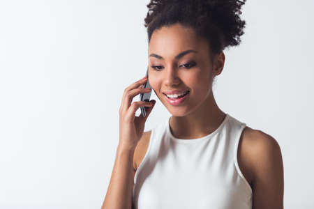 Beautiful Afro-American girl is talking on the mobile phone and smiling, isolated on white