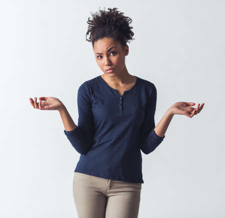 Beautiful Afro-American girl in casual clothes is lifting hands in dismay and looking at camera, isolated on white