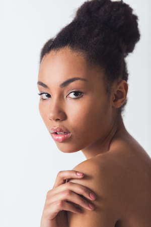 Beautiful Afro-American girl is touching her bare shoulder and looking at camera, isolated on white Stock Photo - 103452556
