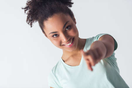 Cheerful Afro-American girl in casual clothes is pointing and looking at camera and smiling, isolated on white