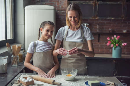 Beautiful mom and daughter in aprons are adding eggs to flour and smiling while using making cookies at home