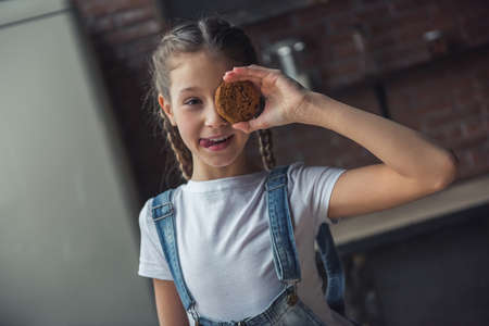 Portrait of little girl holding cookie on her eye, looking at camera and showing a tongue while standing in kitchen at home Archivio Fotografico - 107564110