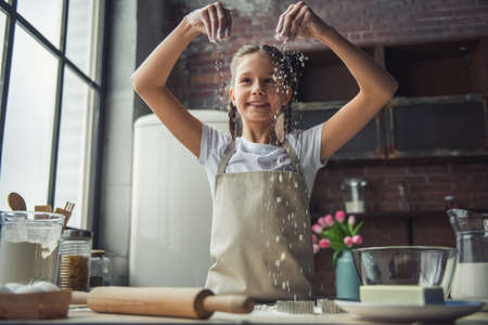 Cute little girl in apron is playing with flour and smiling while cooking in kitchen at home Imagens