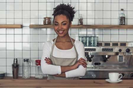 Beautiful Afro American barista in apron is looking at camera and smiling while standing with the crossed arms at the bar counter