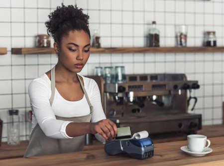 Mooie Afro-Amerikaanse barista in schort gebruikt een betaalterminal terwijl hij aan de bar staat