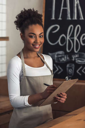 Beautiful Afro American barista in apron is writing down an order, looking at camera and smiling while standing at bar counter 版權商用圖片