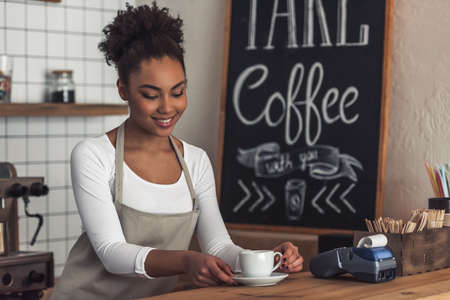 Beautiful Afro American barista in apron is holding a cup and smiling while standing at bar counter
