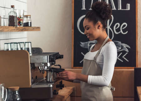 Beautiful Afro American barista in apron is smiling while making coffee using a coffee machine