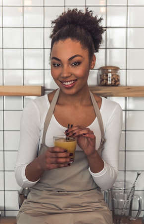 Beautiful Afro American waitress in apron is holding a glass of juice, looking at camera and smiling while sitting on the bar counter