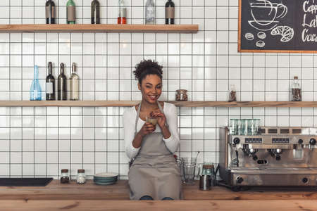 Beautiful Afro American barista in apron is holding a glass of coffee drink, looking at camera and smiling while sitting on the counter near a coffee machine