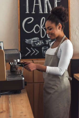 Beautiful Afro American barista in apron is making coffee using a coffee machine and smiling while standing at bar counter