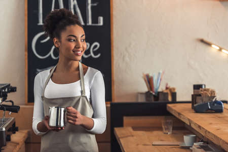 Beautiful Afro American barista in apron is holding a cup of milk, looking away and smiling while standing near a coffee machine 版權商用圖片