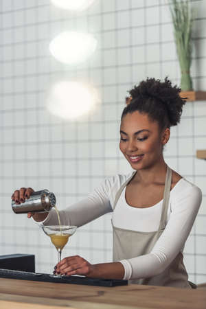 Beautiful Afro American barista in apron is preparing a cocktail in shaker and smiling while standing at bar counter