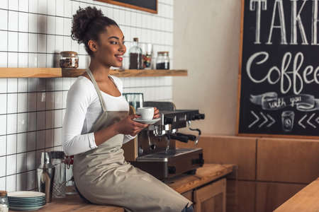 Beautiful Afro American barista in apron is holding a cup of coffee, looking away and smiling while sitting on the counter near a coffee machine