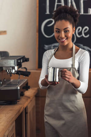 Beautiful Afro American barista in apron is holding a cup of milk, looking at camera and smiling while standing near a coffee machine