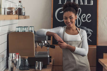 Beautiful Afro American barista in apron is looking at camera and smiling while leaning on the coffee machine Фото со стока