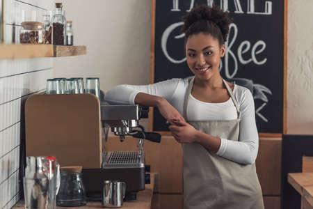 Der schöne afroamerikanische Barista in der Schürze schaut in die Kamera und lächelt, während er sich auf die Kaffeemaschine stützt