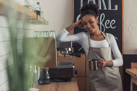 Beautiful Afro American barista in apron is holding a cup, looking at camera and smiling while leaning on the coffee machine 版權商用圖片