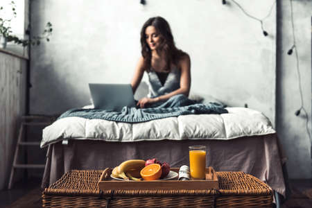 Beautiful young girl is using a laptop and smiling while sitting in bed at home Stock Photo
