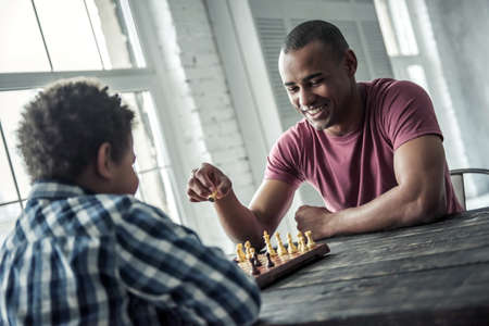 Afro American father and son in casual clothes are playing chess while spending time together at home, man is smiling Stock Photo
