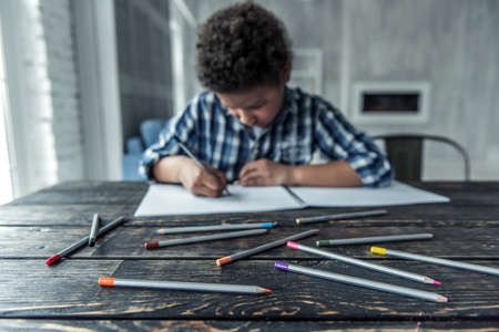 Sad Afro American boy in casual clothes is drawing using colored pencils (in focus) while sitting at the table at home