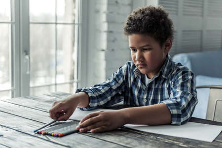 Sad Afro American boy in casual clothes is collecting colored pencils while sitting at the table at home