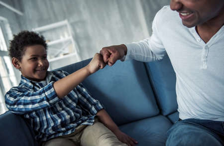 Happy Afro American father and son in casual clothes are doing a fist bump and smiling while sitting on couch at home