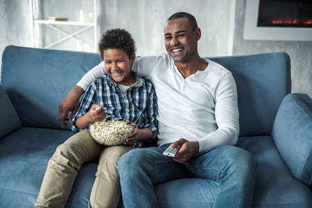 Happy Afro American father and son in casual clothes are watching TV, eating popcorn and smiling while sitting on couch at home 写真素材