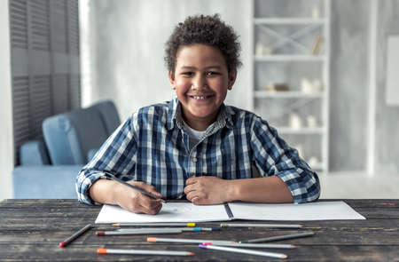 Happy Afro American boy is drawing using colored pencils, looking at camera and smiling while sitting at the table at home Stock Photo