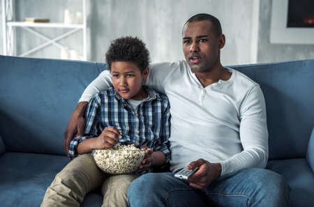 Happy Afro American father and son in casual clothes are watching TV and eating popcorn while sitting on couch at home. Their faces confused