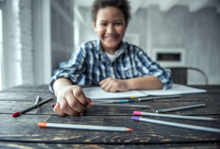 Afro American boy is drawing using colored pencils and smiling while sitting at the table at home, blurred, hand and some pencils in focus Stock Photo