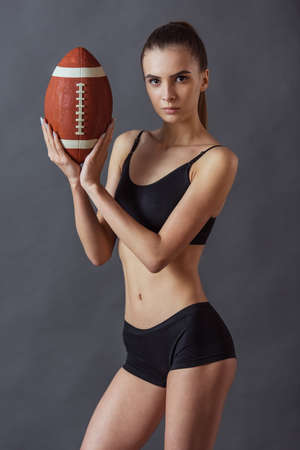 Beautiful girl in sportswear is holding an American football ball and looking at camera, on gray background