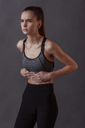 Beautiful girl in sportswear is touching her stomach feeling pain, on gray background
