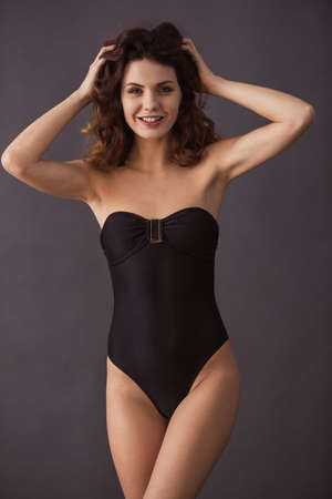 Portrait of a young beautiful sexy girl in a swimsuit on a black background Stockfoto
