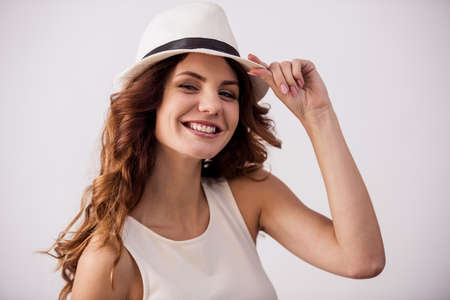 Portrait of a happy young girl with a hat on a white background smiling at the camera 版權商用圖片